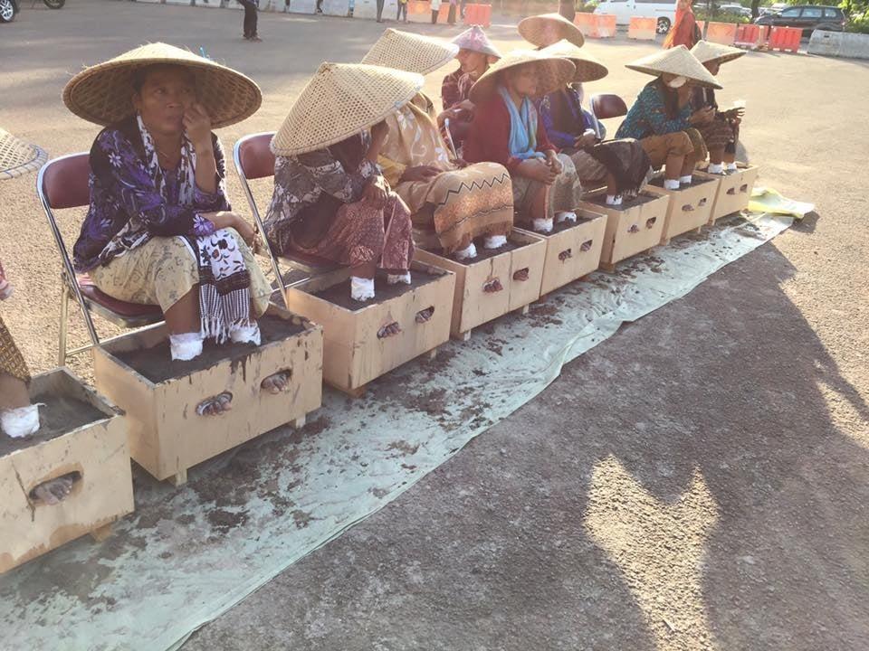 Para petani perempuan Kendeng menanam kaki mereka pada balok semen di depan Istana Negara