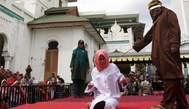 Warga Aceh yang melanggar saat dihukum cambuk dengan rotan. Foto Reuters
