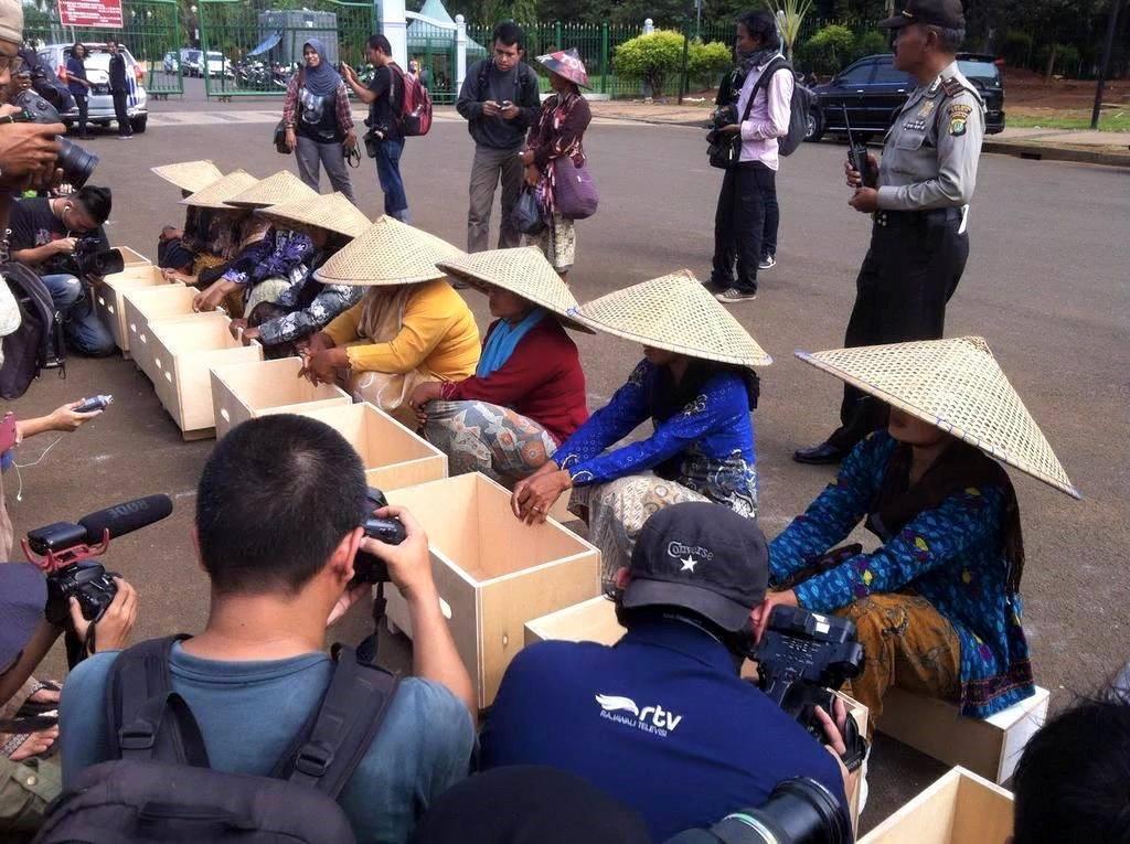para perempuan pejuang sedang bersiap mengecor kaki mereka dengan semen di depan Istana Negara. Foto: Michele